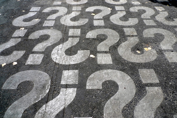 A photo of question marks on pavement representing the Spanish questions on a variety of subjects to use with children.
