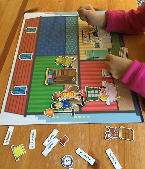 A magnetic board with figure and word magnets helps children learn Spanish house vocabulary.